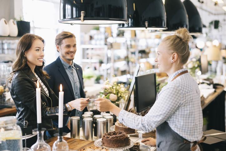 Casal pagando conta no caixa de uma padaria