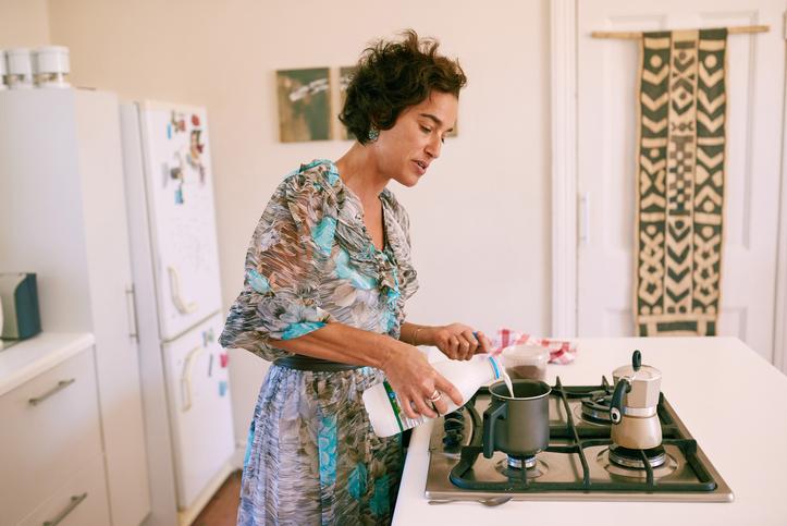 Mulher preparando leite e café no fogão