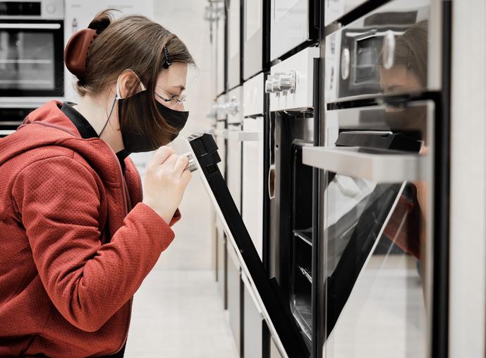 Mulher escolhendo o tipo de forno a comprar