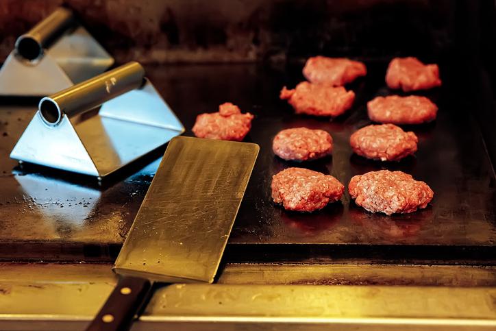 Foto de nove mini hambúrgueres crus que são preparados na chapa. Na frente da chapa tem uma espátula e dois prensadores de hambúrguer ao lado das carnes