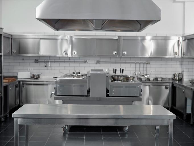 Foto de uma coifa industrial em uma cozinha de restaurante. Embaixo da coifa tem uma mesa e ao fundo armários e equipamentos de restaurante.
