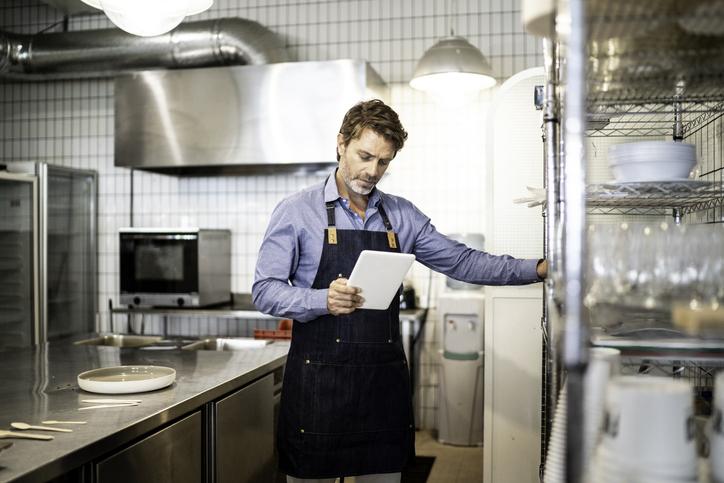 Foto de um homem adulto com um avental azul em uma cozinha que olha e segura para uma lista de equipamentos para lanchonete.