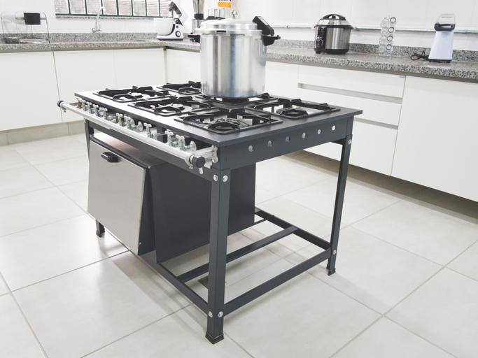 Foto de um fogão industrial com uma panela de pressão em cima na cozinha de um restaurante.