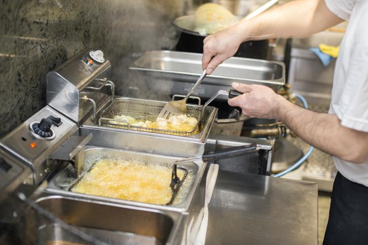 Foto de um homem que prepara batatas fritas em duas fritadeiras em uma cozinha